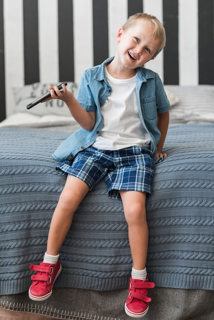 Smiling boy sitting on bed holding smart phone Free Photo