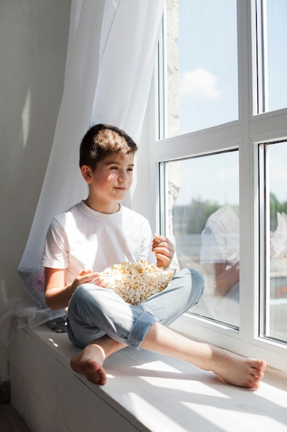 Smiling boy sitting on window sill holding bowl of popcorn and looking outside Free Photo