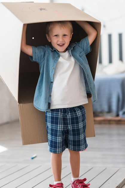 Smiling boy standing with cardboard box over his head Free Photo