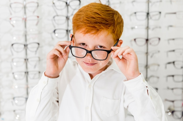Smiling boy with freckle on his face wearing spectacle and looking at camera Free Photo