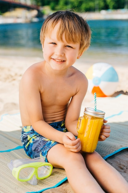 Smiling boy with glass juice and sitting on beach Free Photo