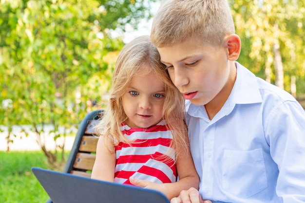 Smiling brother and sister sitting on bench in park and playing on laptop Premium Photo