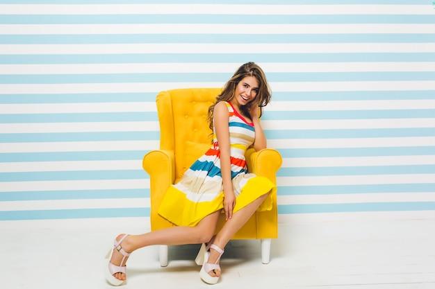 Sorridente ragazza bruna in abito estivo luminoso in posa all'interno, seduto nella grande poltrona gialla. ritratto di splendida giovane donna con i capelli castano chiaro che riposa nella sua stanza sulla parete a strisce. Foto Gratuite