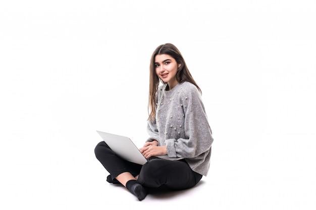 Улыбающаяся брюнетка девушка модель в сером свитере сидит на полу и работает в студии на своем ноутбуке Бесплатные Фотографии