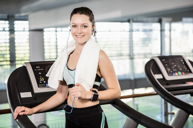 Smiling brunette on treadmill looking at the camera at the gym Premium Photo