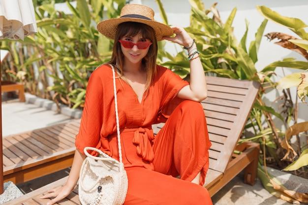 スタイリッシュなオレンジ色の衣装とプールの近くのデッキチェアで身も凍るよう麦わら帽子のブルネットの女性の笑みを浮かべてください。 無料写真