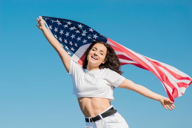 Улыбающаяся брюнетка женщина в белой одежде держит большой флаг сша Бесплатные Фотографии