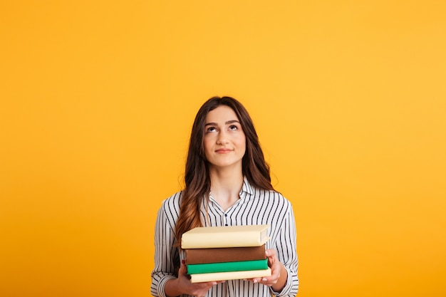 Smiling brunette woman in shirt holding books and looking up Free Photo