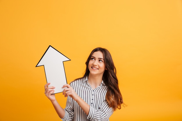 Smiling brunette woman in shirt pointing with paper arrow up Free Photo
