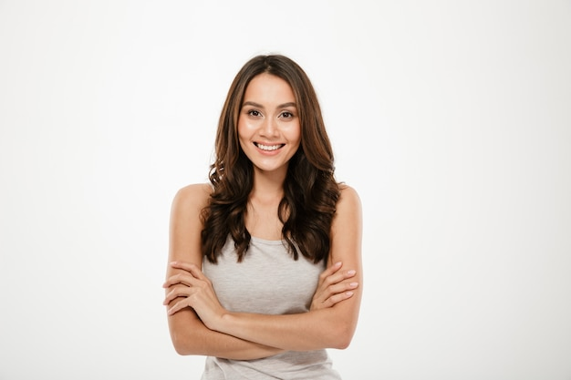 Smiling brunette woman with crossed arms looking at the camera over gray Free Photo