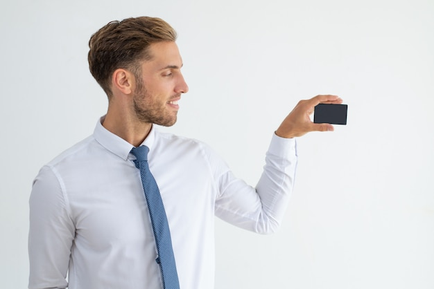 Smiling business leader showing blank business card Free Photo