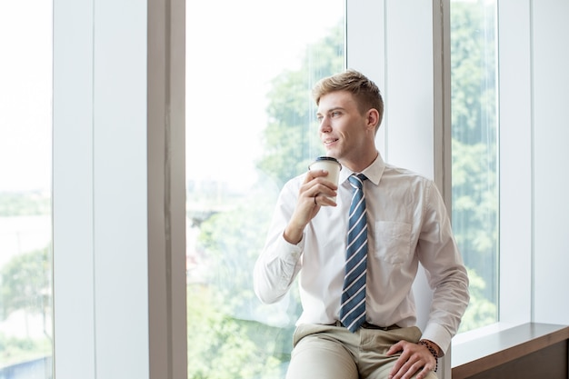 Smiling business man drinking on window sill Free Photo
