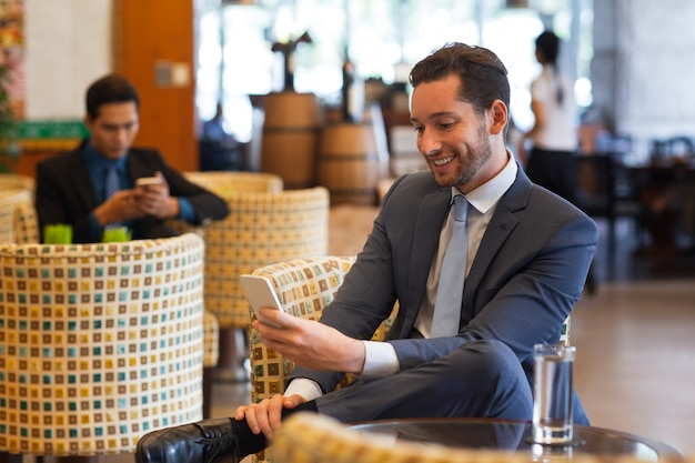 Smiling business man texting on smartphone in cafe Free Photo