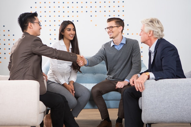 Smiling business partners shaking hands in lounge Free Photo