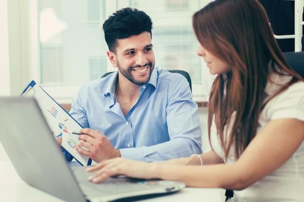 彼らのオフィスでラップトップコンピューターを使用してビジネス人々の笑顔 Premium写真