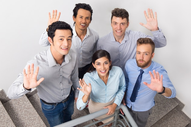 Smiling Business People Waving on Office Stairway Photo ...