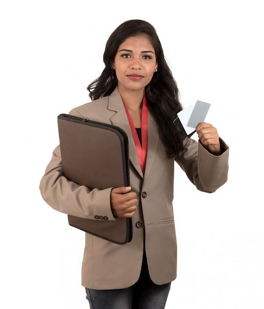 空白の名刺やidカードをホワイトスペースにかざす笑顔のビジネス女性 Premium写真