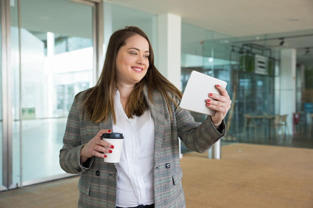 Smiling business woman holding tablet and drink outdoors Free Photo