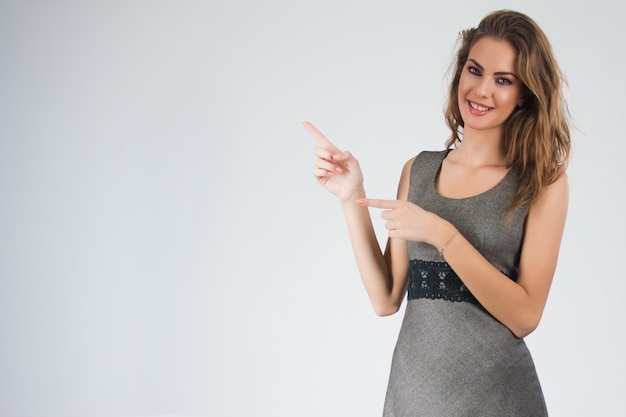 Smiling business woman pointing finger on copy space. isolated portrait Free Photo
