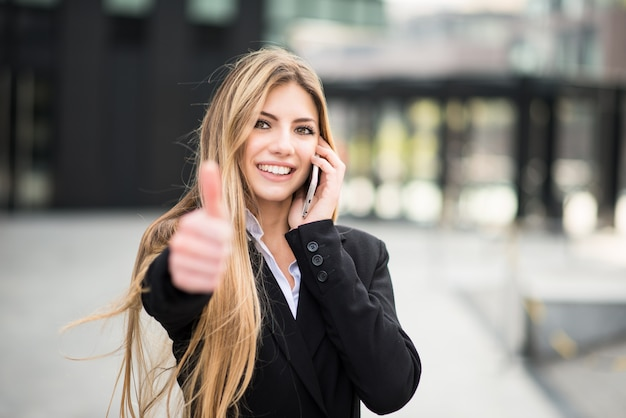 Smiling business woman talking on the phone and thumbs up Premium Photo