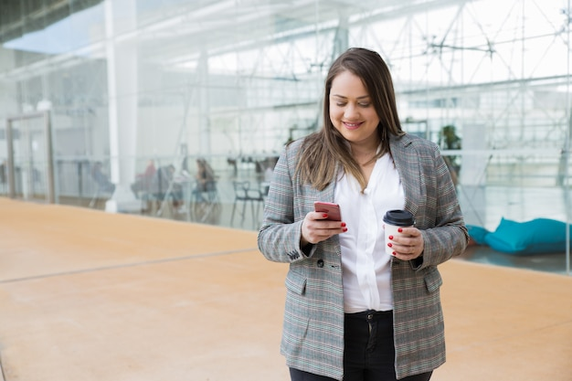 Smiling business woman texting on smartphone outdoors Free Photo