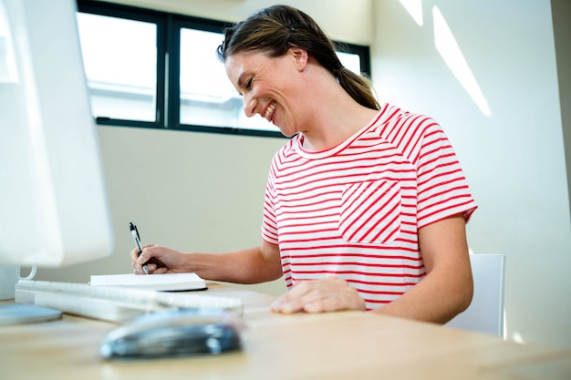 Smiling business woman writing in her notepad on her desk Premium Photo