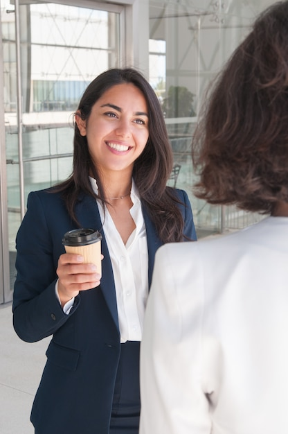 Smiling business women talking and drinking coffee Free Photo