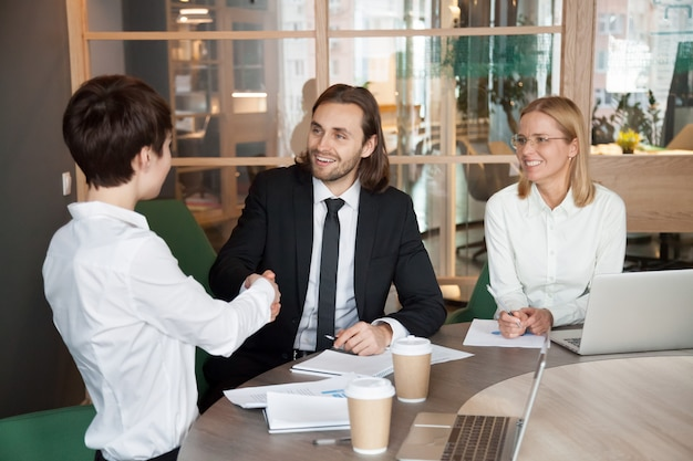 Smiling businessman and businesswoman shaking hands at group meeting negotiations Free Photo