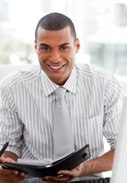 Smiling businessman consulting his agenda Premium Photo