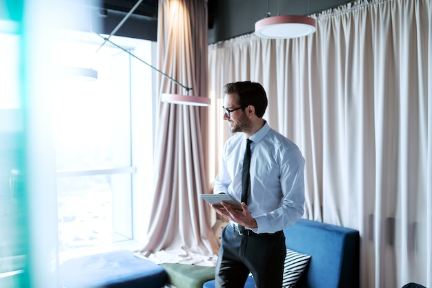 Smiling businessman in formal wear looking away and using tablet while standing in the office. Premium Photo