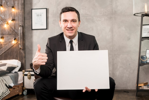 Smiling businessman holding blank paper and gesturing thumb up Free Photo