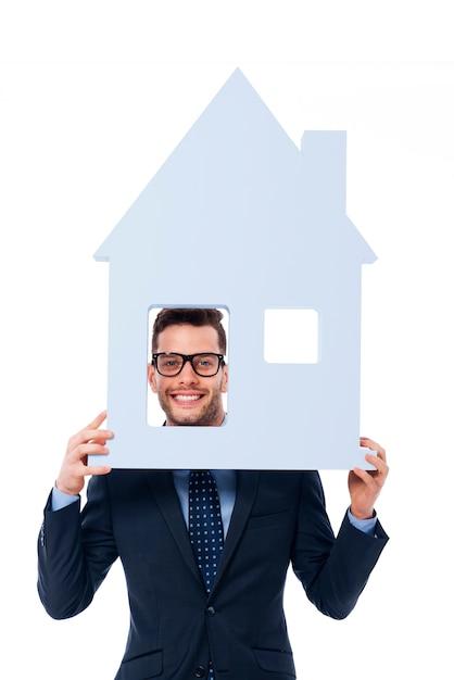 Smiling businessman holding house sign Free Photo