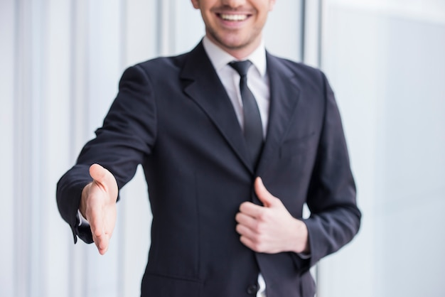 Smiling businessman is wearing in suit, handshake to you. Premium Photo