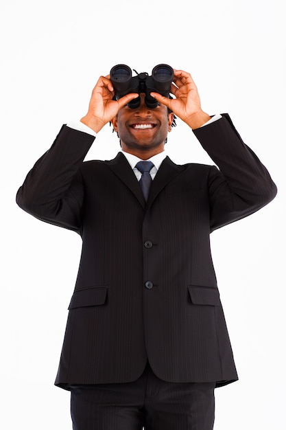 Smiling businessman looking through binoculars Premium Photo