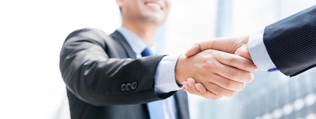 Smiling businessman making handshake with his partner outdoors in the city Premium Photo