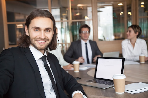 Smiling businessman manager in suit looking at camera at meeting Free Photo