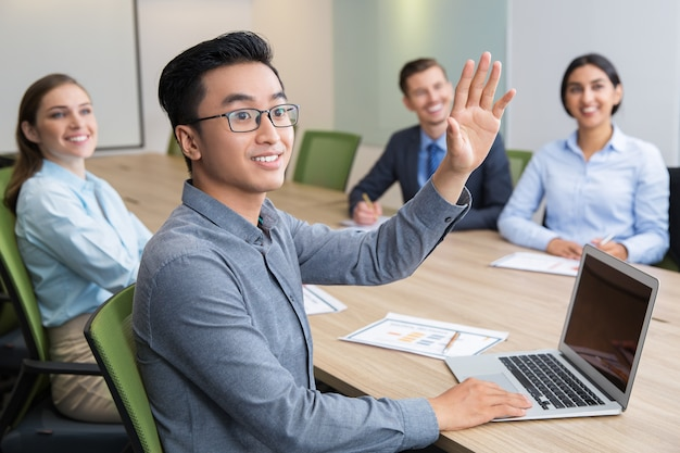 Smiling businessman raising hand at conference Free Photo
