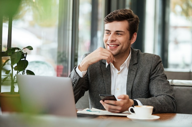 Smiling businessman sitting by the table in cafe with laptop computer and smartphone while looking away Free Photo