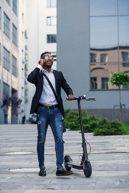 現代のビジネスの建物の近くの電動スクーターで笑顔の実業家 Premium写真
