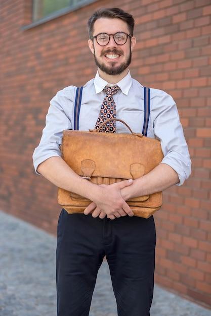 L'uomo d'affari sorridente con la vecchia valigetta in pelle retrò contro il muro di mattoni rossi Foto Gratuite