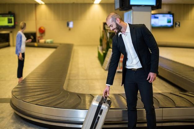 Uomo d'affari sorridente con borsa trolley in area di attesa Foto Gratuite
