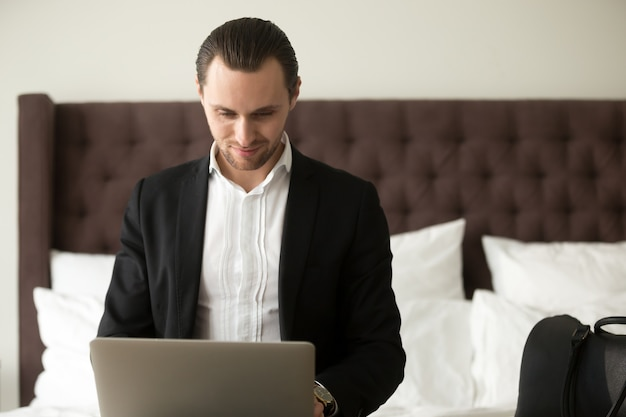Smiling businessman working on laptop in bedroom. Free Photo