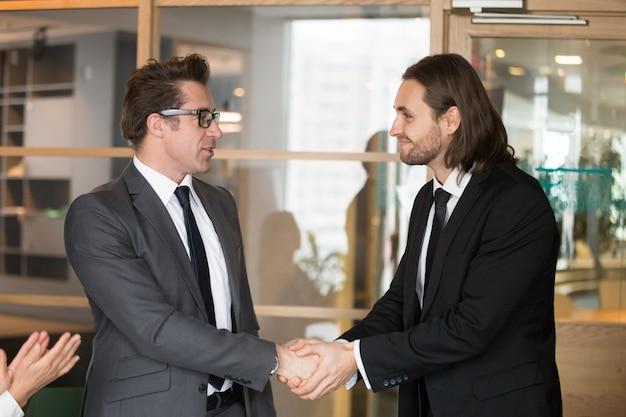 Smiling businessmen shaking hands, making deal, gratitude or promotion concept Free Photo