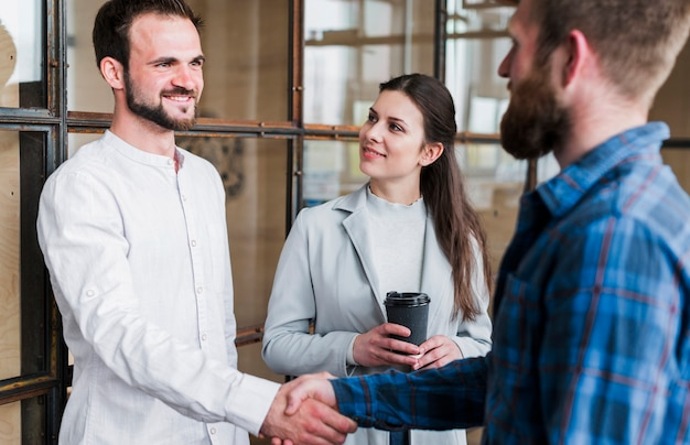 Smiling businesspeople shaking hand at office Free Photo