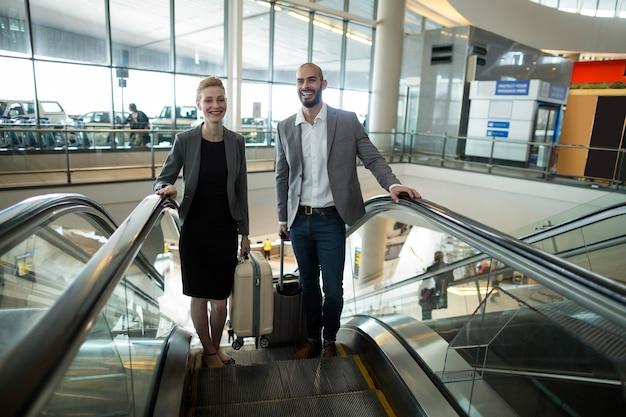 エスカレーターで荷物を上げて笑顔のビジネスマン 無料写真