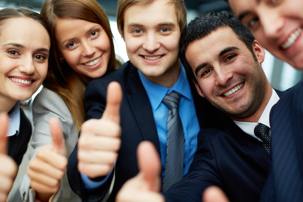 Smiling businessteam holding their thumbs up Free Photo