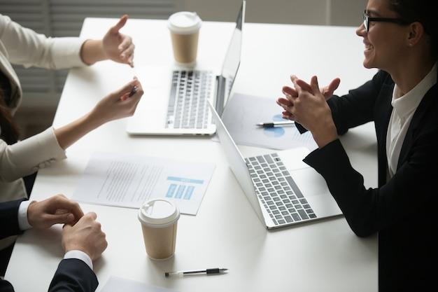 Улыбается бизнесвумен, наслаждаясь разговор с коллегами во время совместной работы с ноутбуками Бесплатные Фотографии