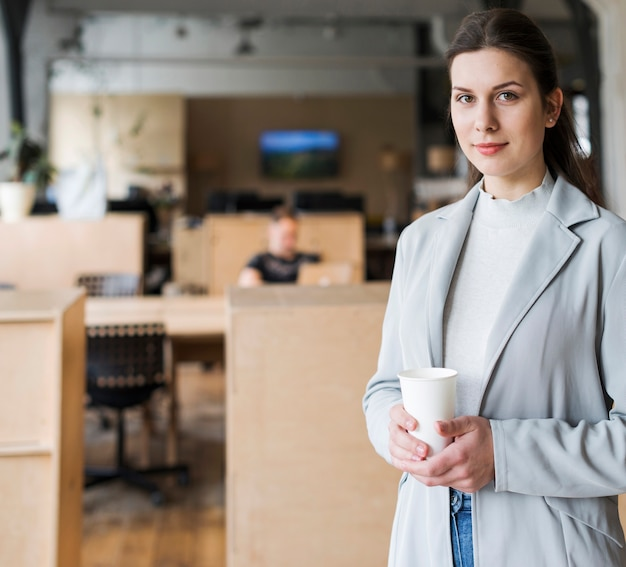 Smiling businesswoman holding disposable coffee cup in workplace Free Photo