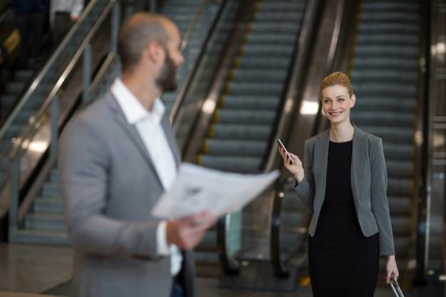 Улыбаясь бизнесвумен, взаимодействуя с бизнесменом в зоне ожидания Бесплатные Фотографии