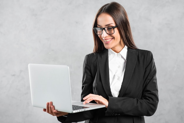 Smiling businesswoman looking at laptop in her hand against concrete wall Free Photo